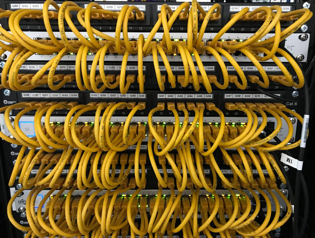 Image of UniFi Switches in Communications cabinet patched with 25cm Yellow cables.